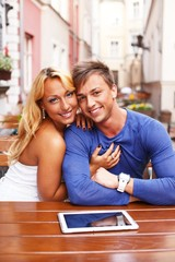 Stylish happy young couple with tablet pc