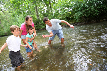 Adults with kids throwing pebbles in river