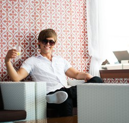 Handsome young man in sunglasses sitting