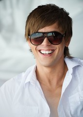 Happy smiling handsome young man in sunglasses and white shirt