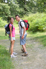 Couple in countryside walking on a trekking path