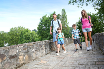 Family on a rambling journey crossing roman bridge