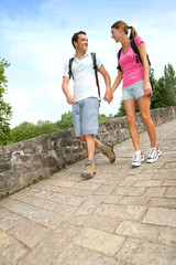 Couple on a rambling day crossing a roman bridge