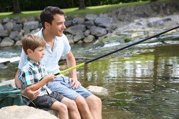 Father teaching son how to fish in river