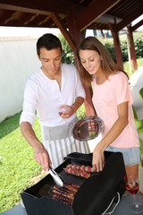 Couple cooking meat on grill at home