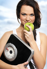 Portrait of a young and healthy woman holding an apple