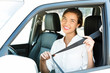 Attractive young woman in a car fastens seat belt