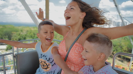 mom with two kids ride on the Ferris wheel