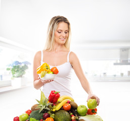 A young blond woman and a pile of fresh fruits and vegetables