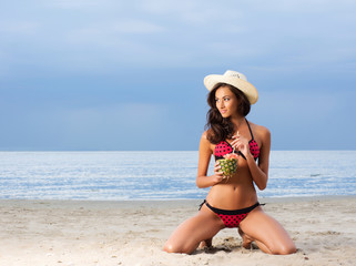 A young brunette woman drinking a cocktail on the beach