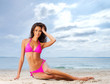 A young brunette woman in a pink swimsuit relaxing on the beach