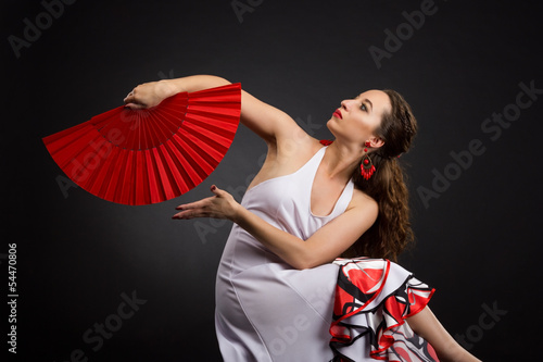 Young spanish woman dancing flamenco on black