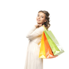 A young woman in a white dress holding shopping bags