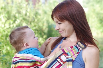 Mother carrys little son age of 10 months in baby sling
