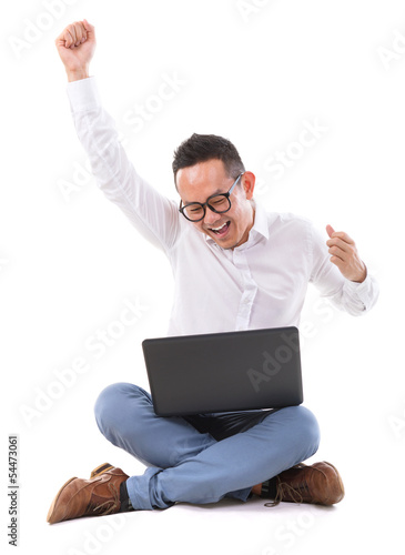 Excited Asian man using laptop