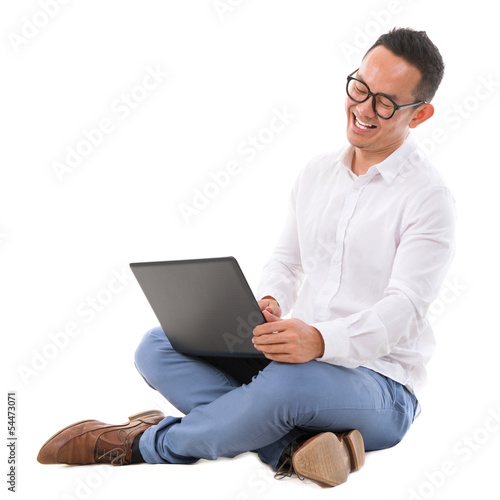 Excited Asian male using laptop