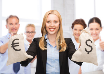 businesswoman holding money bags with dollars