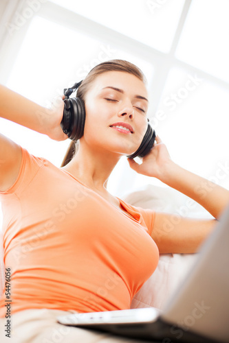 woman with headphones and laptop at home