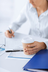 woman with coffee filling in blank paper