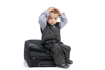 little boy sitting on a suitcase