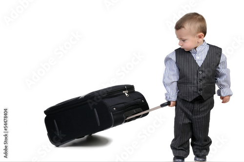 small boy carrying a suitcase