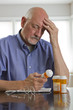 Older man with prescription medications, vertical