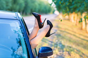 Woman's legs in highheel shoes out of a car window