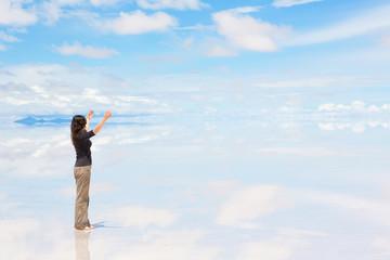 Woman standing on Salar de Uyuni with raised hands