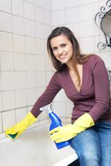 Happy woman cleaning  bathtub