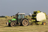 Tractor collecting haystack in the field at the airfield