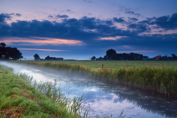 Dutch farmland with canal at dusk