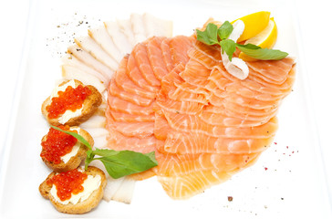 sandwiches with caviar and sliced fish on a white plate