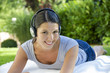 woman lying on blanket with headphones