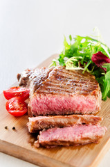 Grilled ribeye steak served with healthy salad