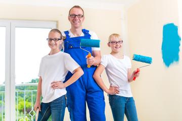 Familie - Vater und Kinder streichen eine Wand
