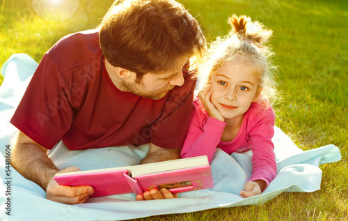 Father reading a book to his daughter in the garden