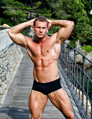 Handsome young muscle man outdoors, showing muscular body