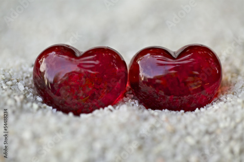 Symbol of love, two red hearts with stones on the sand.