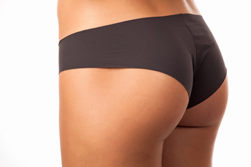 Closeup view of female buttocks in lingerie against white