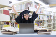 Happy graduate at library with laptop