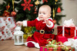 baby girl dressed as Santa Claus in front of Christmas tree with