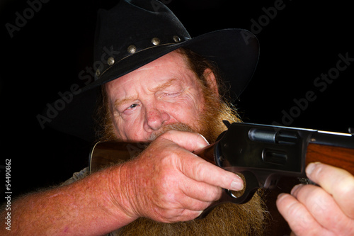 Close up of an older cowboy about to pull the trigger