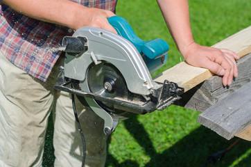 Handyman using hand-held saw machine outdoors