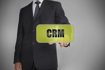 Businessman selecting green tag with the word crm written on it