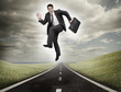 Businessman jumping on a road