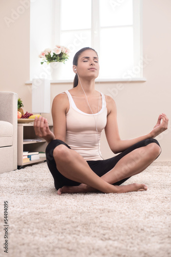Yoga at home. Beautiful young women meditating at home while sit