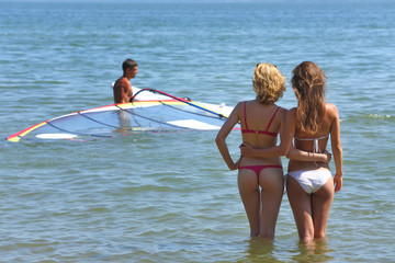 Two young sexy girlfriends flirt and look at the man on windsurf