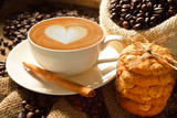 Naklejka A cup of cafe latte with coffee beans and cookies