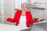 Lachende ältere Frau am Arbeitsplatz im Büro