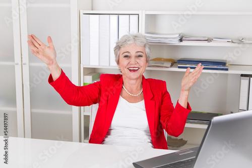 Seniorchefin - Frau mit grauen Haaren freut sich im Büro